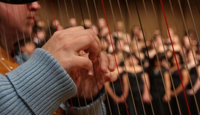 Hands playing a harp with choir students in background