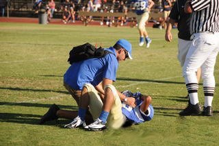 Chris Khal tending to football student